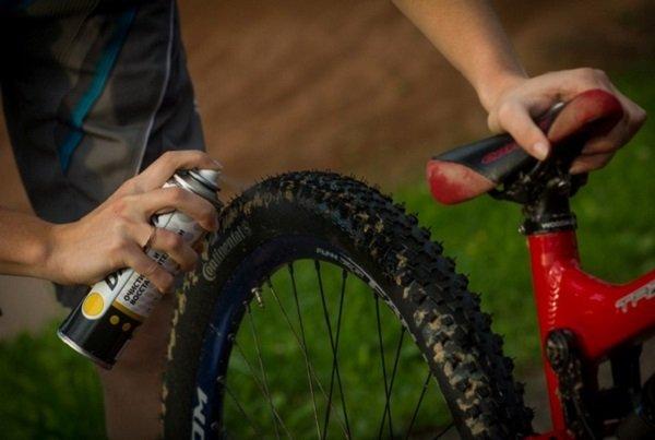 нанесение спрея на колесо велосипеда