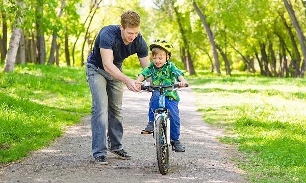 езда ребенка на двухколесном велосипеде